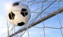 Fußball fliegt vor blauen Himmel ins Tor, mit Gegenlicht